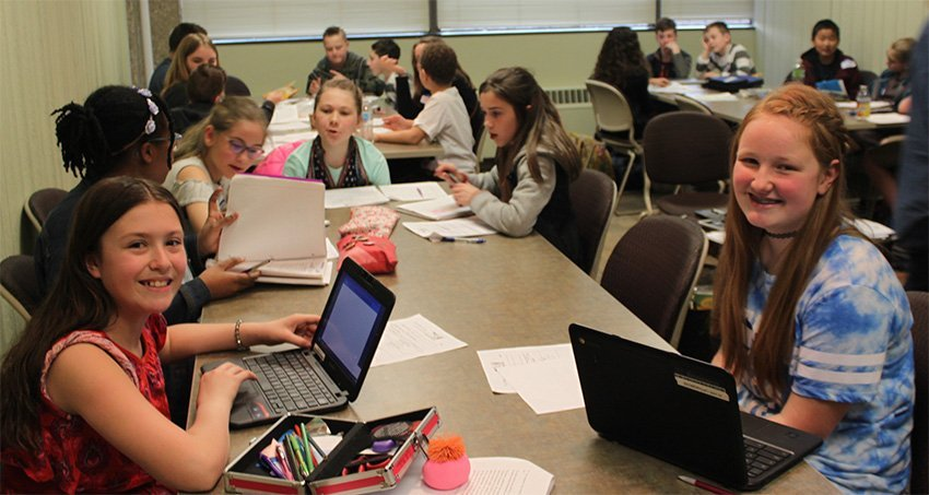 Students working in groups with laptops, notebooks, pens, and paper