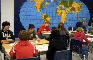 Students at desks. An oval projection of the earth fills the back wall.
